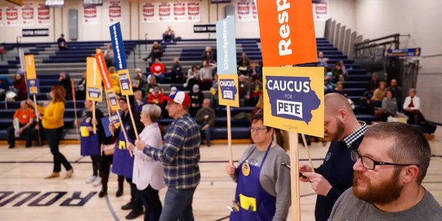 Supporters of Democratic presidential candidate former South Bend, Ind., Mayor Pete Buttigieg stand at a caucus site at Roosevelt Hight School, Monday, Feb. 3, 2020, in Des Moines, Iowa. (AP Photo/Andrew Harnik)