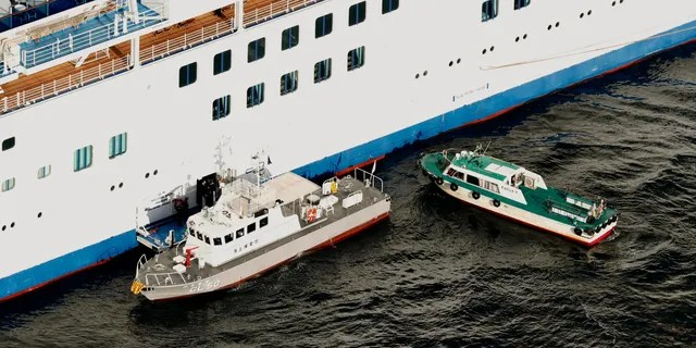 Japan Coast Guard's patrol boat, left, is brought alongside the cruise ship Diamond Princess to take passengers tested positive for coronavirus to hospitals off Yokohama, south of Tokyo, Wednesday, Feb. 5, 2020. (Hiroko Harima/Kyodo News via AP)