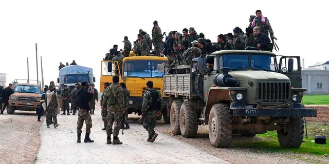 In this photo released Feb. 5, 2020 by the Syrian official news agency SANA, shows Syrian government forces entering the village of Tel-Sultan, in Idlib province, northwest Syria. (SANA via AP)