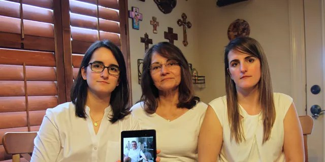 In this Feb. 15, 2019 file photo, Dennysse Vadell sits between her daughters Veronica, right, and Cristina holding a digital photograph of father and husband Tomeu who is currently jailed in Venezuela with five other executives from Houston-based Citgo, in Katy, Texas, Friday. (AP Photo/John L Mone, File, File)