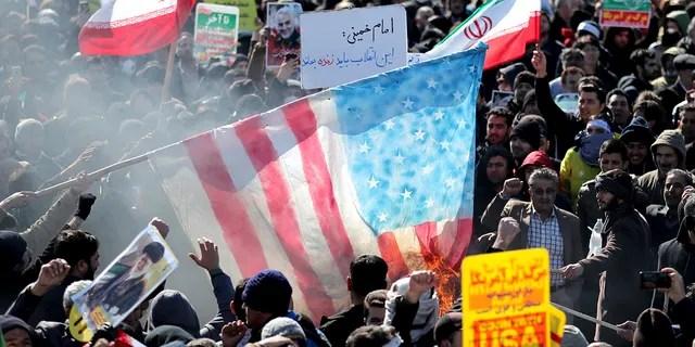 Iranians burn a U.S. flag during a rally at Azadi (Freedom) Square celebrating the 41st anniversary of the Islamic Revolution, in Tehran, Iran. (AP Photo/Ebrahim Noroozi)