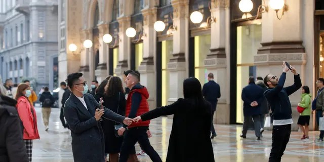 Tourists wearing sanitary masks move a few steps of dance, in downtown Milan, Italy, Sunday, Feb. 23, 2020. (AP Photo/Antonio Calanni)