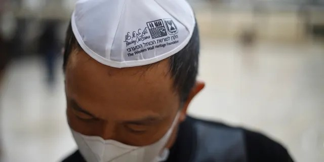 A man wears a face mask as he visits the Western Wall, the holiest site where Jews can pray in Jerusalem's old city, Sunday, Feb. 16, 2020. (AP Photo/Ariel Schalit)