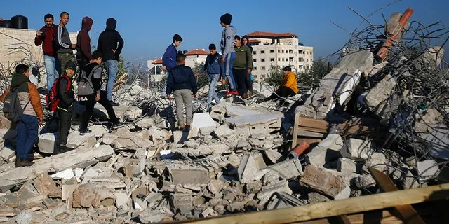Palestinians inspect a house after it was demolished by the Israeli army in the West Bank city of Jenin on Thursday. (AP)