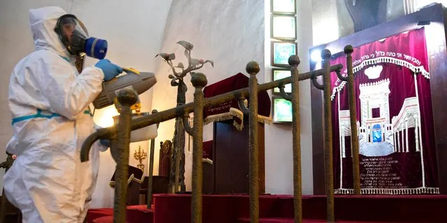 Workers spray disinfectant as a precaution against the coronavirus at the Great Synagogue in Tel Aviv, Israel, Tuesday, March 17, 2020.