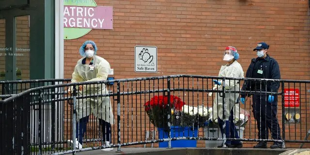 Emergency room nurses gather flowers donated to the hospital staff on a ramp outside Elmhurst Hospital Center's ER after a neighbor dropped them off, Saturday, March 28, 2020. The Queens borough hospital has been heavily taxed treating coronavirus patients in recent weeks. New York leads the nation in the number of cases, according to Johns Hopkins University, which is keeping a running tally. (AP Photo/Kathy Willens)