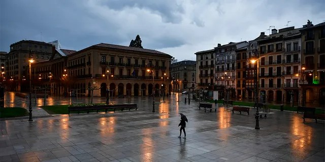 A person walks through an empty Plaza del Castillo square in the old city, in Pamplona, northern Spain, Sunday, March 15, 2020. Spain's prime minister announced a two-week state of emergency from Saturday in a bid to contain the new coronavirus outbreak.  (AP Photo/Alvaro Barrientos)