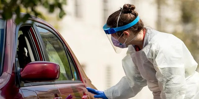 A medical worker asks a young man to lower his window like a COVID-19 test at a driving test site at Trinity University last week in Washington. (AP Photo / Andrew Harnik)