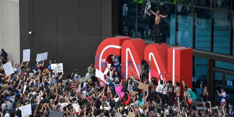 Demonstrators paint on the CNN logo during a protest, Friday, May 29, 2020, in Atlanta, in response to the death of George Floyd in police custody on Memorial Day in Minneapolis. (Associated Press)