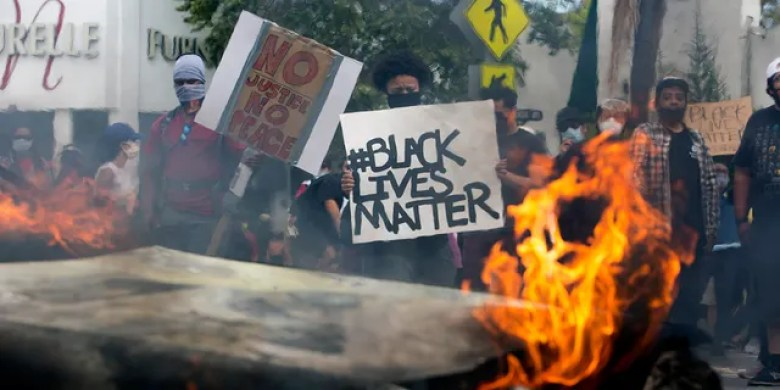 People hold signs and shout behind a burning police vehicle in Los Angeles, Saturday, May 30, 2020, during a protest over the death of George Floyd. (Associated Press)