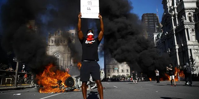 A vehicle is on fire behind a protester holding a sign during a rally on Saturday, May 30, 2020, in Philadelphia, over the death of George Floyd, a black man who died after being taken into police custody in Minneapolis. Floyd died after an officer pressed his knee into his neck for several minutes even after he stopped moving and pleading for air on Memorial Day. (AP Photo/Matt Rourke)