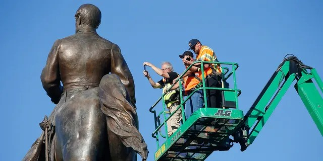 An inspection crew from the Virginia Department of General Services inspect the statue of Confederate Gen. Robert E. Lee on Monument Avenue June 8, in Richmond, Va. Virginia Gov. Ralph Northam has ordered the removal of the statue. (AP Photo/Steve Helber)