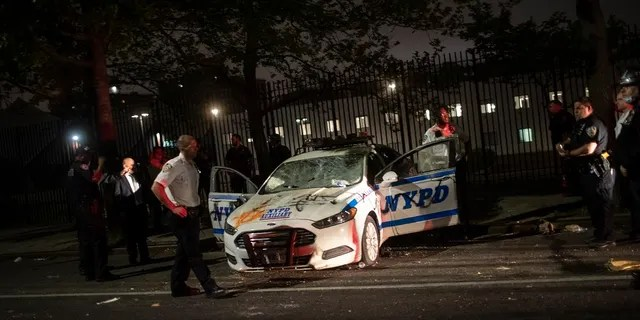 Policemen surround a NYPD vehicle after it was vandalized by protestors over the death of George Floyd, a black man who was in police custody in Minneapolis, on Saturday, May 30, 2020, in the Brooklyn borough of New York. (AP Photo/Wong Maye-E)