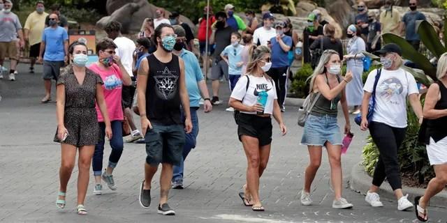 Гости в масках прогуливаются по SeaWorld, поскольку он вновь открылся с новыми мерами безопасности, принятыми в четверг, 11 июня 2020 года, в Орландо, штат Флорида. Парк был закрыт с середины марта, чтобы остановить распространение нового коронавируса. (Ассошиэйтед Пресс)