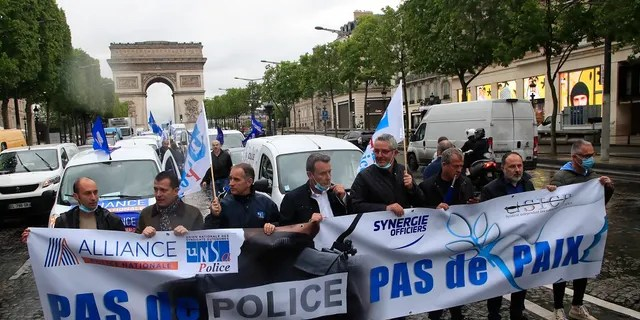 """French police unionists demonstrating with a banner reading, """"No police, no peace,"""" on the Champs-Elysee avenue near the Arc de Triomphe this past Friday in Paris. (AP Photo/Michel Euler)"""
