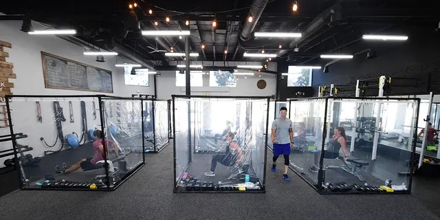 Peet Sapsin leads a class at Inspire South Bay Fitness with students behind plastic sheets in their workout pods on June 15.