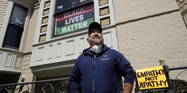 James Juanillo posing outside of his home in San Francisco on Sunday. (AP Photo/Jeff Chiu)