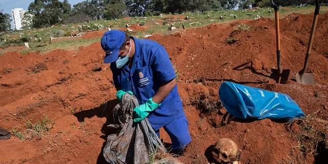 Работник кладбища эксгумирует тело человека, похороненного три года назад на кладбище Вила-Формоза, которое не взимает плату с семей за могилы в Сан-Паулу, Бразилия, в пятницу, 12 июня 2020 года. Через три года после захоронений останки обычно эксгумируются и хранятся в пластиковых пакетах, чтобы освободить место для новых захоронений, количество которых увеличилось на фоне нового коронавируса. (AP Photo / Андре Пеннер)