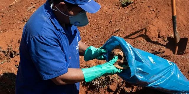 Работник кладбища кладет череп в сумку, убирая тело человека, похороненного три года назад на кладбище Вила-Формоза, которое не взимает плату с семей за могилы, в Сан-Паулу, Бразилия, в пятницу, 12 июня 2020 года. Три года после захоронений останки обычно эксгумируются и хранятся в полиэтиленовых пакетах, чтобы освободить место для новых захоронений, количество которых увеличилось на фоне нового коронавируса. (AP Photo / Андре Пеннер)