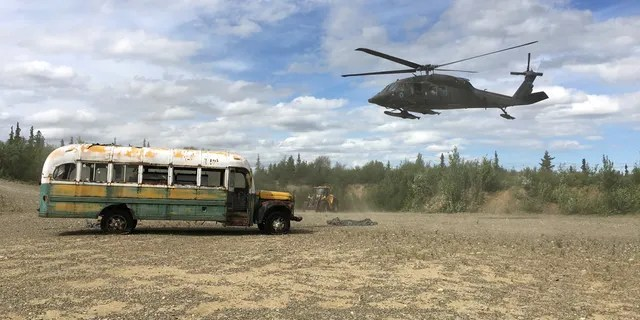"""An Alaska Army National Guard UH 60 Blackhawk helicopter hovers near """"Bus 142,"""" made famous by the """"Into the Wild"""" book and movie."""