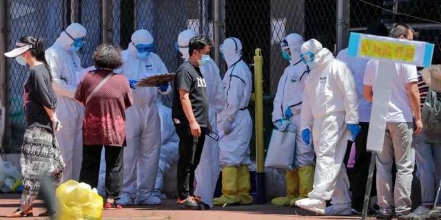 Рабочие в защитных костюмах проверяют имена людей в списке, которые либо жили рядом с оптовым рынком Xinfadi, либо посещали рынок, чтобы пройти тест на нуклеиновые кислоты на стадионе в Пекине, воскресенье, 14 июня 2020 года.