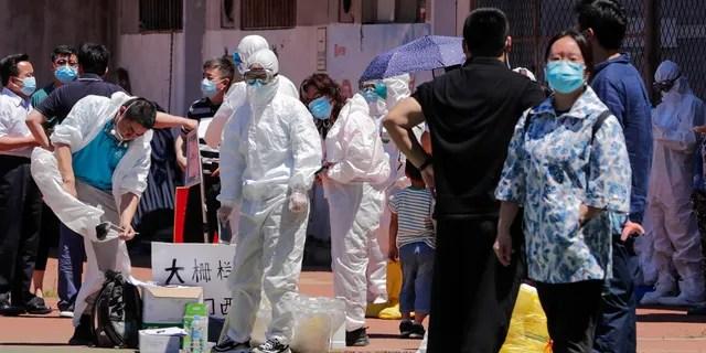 Рабочие надевают защитные костюмы, ожидая, пока люди, живущие на оптовом рынке Xinfadi, приедут, чтобы пройти тест на нуклеиновые кислоты на стадионе в Пекине, в воскресенье, 14 июня 2020 года.
