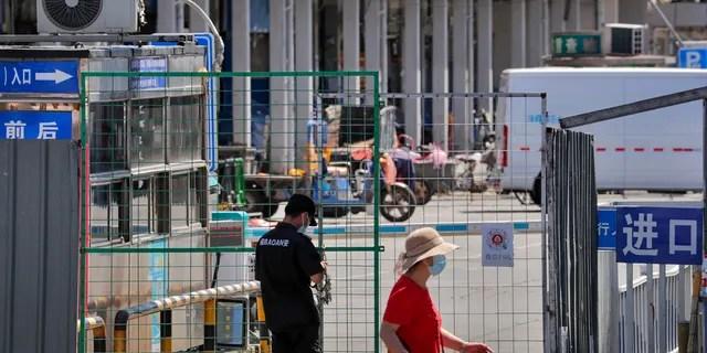 Охранник запирает цепью забор главного входа оптового рынка морепродуктов, который был закрыт для проверки в Пекине, в воскресенье, 14 июня 2020 года.