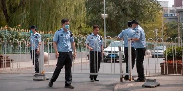 Полицейские проводят баррикаду через дорогу, ведущую в жилой район недалеко от района оптового продовольственного рынка Xinfadi в Пекине, в субботу, 13 июня 2020 года.