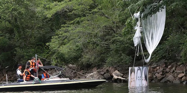 Police officers ride a boat to collect a balloon carrying a banner with images of North Korean leader Kim Jong Un, the late leader Kim Il Sung and Kim Yo Jong, the powerful sister of Kim Jong Un, released by Fighters For Free North Korea, in Hongcheon, South Korea, Tuesday, June 23, 2020. (Yang Ji-woong/Yonhap via AP)