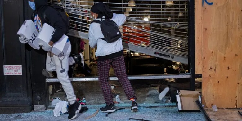 People exit damaged stores after the glass was knocked out in the Chelsea neighborhood of New York, June 1. (AP Photo/Craig Ruttle)