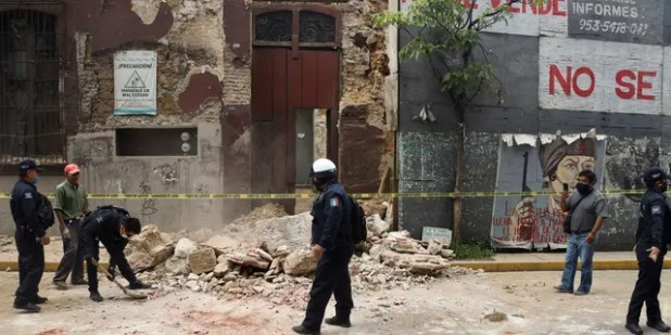 A policeman removes debris from an earthquake-damaged building in Oaxaca, Mexico, on June 23.