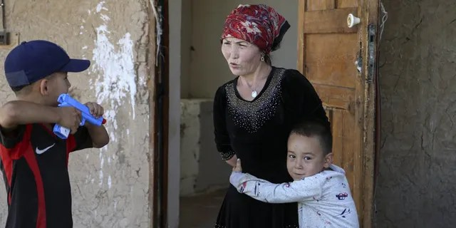 Alif Baqytali hugs his mother, Gulnar Omirzakh, at their new home in Shonzhy, Kazakhstan. Omirzakh, a Chinese-born ethnic Kazakh, says she was forced to get an intrauterine contraceptive device, and that authorities in China threatened to detain her if she didn't pay a large fine for giving birth to Alif, her third child.