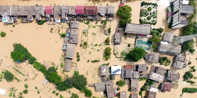 In this aerial photo published by the Xinhua news agency, a village was flooded on July 13 in the Sanjiao County of Yongxiu County, in east China's Jiangxi Province.