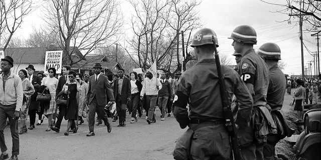 Federal Army troops guard civil rights marchers along route 80, the Jefferson Davis Highway, during the Selma to Montgomery Civil Rights March on March 25, 1965, in Montgomery, Ala.