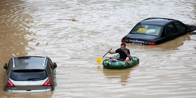 In this photo published by the Xinhua News Agency, a man paddles an inflatable boat in front of submerged cars during a flood in Rongshui County, Guangxi Zhuang Autonomous Region in southern China, the 11 July.