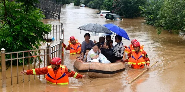 Rescuers evacuate residents on a raft in the floodwaters of Jiujiang, central China's Jiangxi Province, July 8.