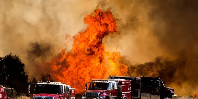Flames flare behind fire trucks at the Apple Fire in Cherry Valley, Calif., Saturday, Aug. 1, 2020.