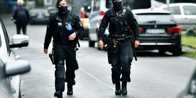Police secure a street where five dead children were found in an apartment house in Solingen, Germany, Thursday, Sept. 3, 2020. (AP Photo/Martin Meissner)