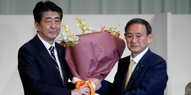 Japanese Prime Minister Shinzo Abe receives flowers from Chief Cabinet Secretary Yoshihide Suga after being elected as the new head of Japan's ruling party in September, Septa-14, the Liberal Democratic Party (LDP) leadership election in Tokyo.  The ruling LDP elects its new leader in an internal vote to elect a successor to Prime Minister Shinzo Abe, who announced his resignation last month due to illness.  (AP Photo / Eugene Hoshiko, Pool)