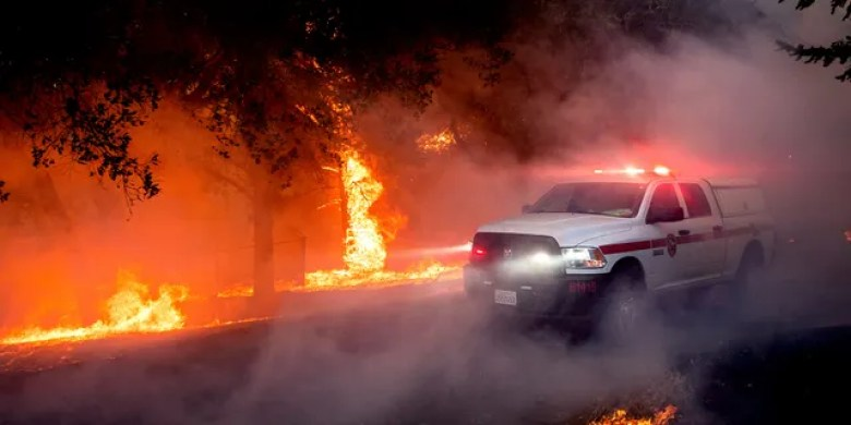 Flames from the Glass Fire lick up a tree in St. Helena, Calif., Sunday, Sept. 27, 2020.