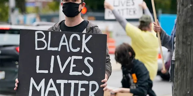 A protester holds up a Black Lives Matter sign near the debate hall, Tuesday, Sept. 29, 2020, in Cleveland. The first presidential debate between Republican candidate President Donald Trump and Democratic candidate and former Vice President Joe Biden is being held in Cleveland Tuesday. (AP Photo/Tony Dejak)