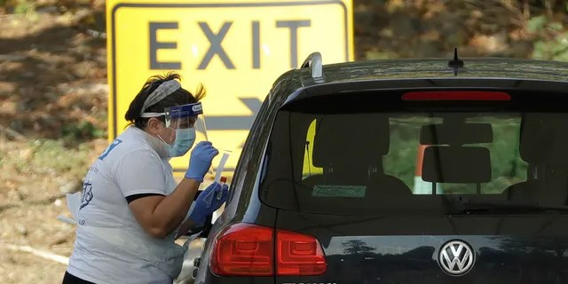 A person is tested for COVID-19 at a drive-through testing centre in a car park at Chessington World of Adventures, in Chessington, Greater London, Saturday, Sept. 19, 2020.