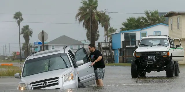 Jeff Williams gets back in his vehicle to try to get it out of the flooded road Monday, Sept. 21, 2020, in Surfside, Texas.