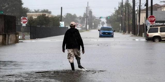 A man walks through a street flooded by Tropical Storm Beta Monday, Sept. 21, 2020, in Galveston, Texas.