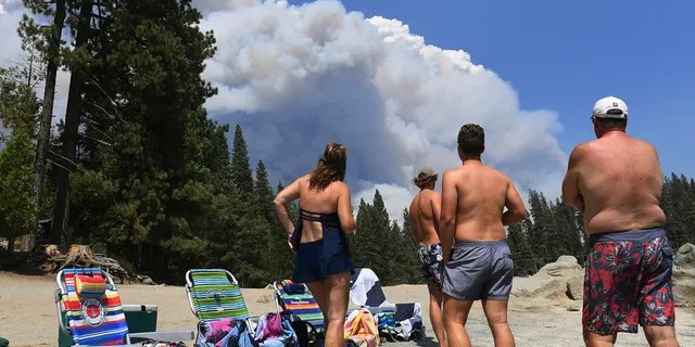 A family from Ventura County watches, from the shore of Shaver Lake, the billowing smoke from the Creek Fire, Saturday, Sept. 5, 2020, northeast of Fresno, Calif.