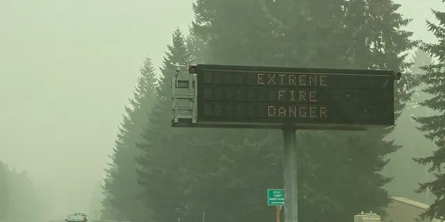 A fire warning sign is seen through the smoke in Sandy, Ore., on Monday, Sept. 14, 2020.