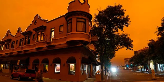 A woman crosses a street by in front of a hotel as smoke from wildfires darken the morning sky Wednesday, Sept. 9, 2020, in Sausalito, California.