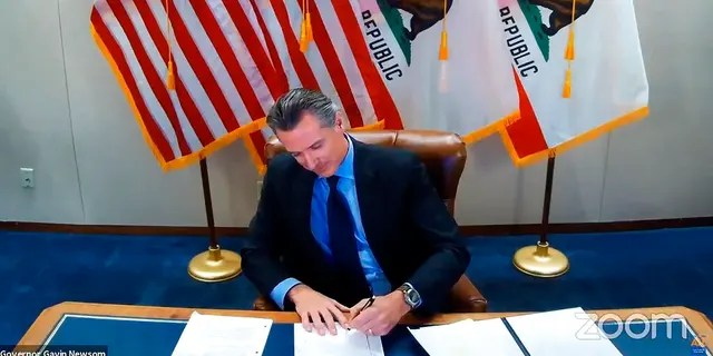 This image made from video from the Office of the Governor shows California Gov. Gavin Newsom signing into law a bill that establishes a task force to come up with recommendations on how to give reparations to Black Americans.