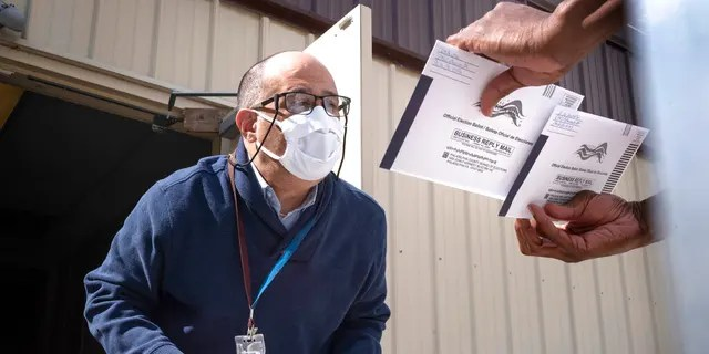 An employee of the Philadelphia Commissioners Office examines ballots at a satellite election office at Overbrook High School in Philadelphia. (AP Photo/Laurence Kesterson)
