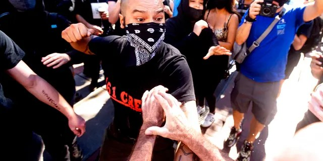 A counter-protester, who declined to give his name, prepares to hit a conservative free speech rally organizer in San Francisco on Saturday, Oct. 17, 2020. About a dozen pro-Trump demonstrators were met by several hundred counter-protesters as they tried to rally. (AP Photo/Noah Berger)